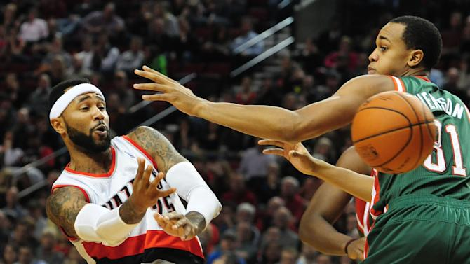 Portland Trail Blazers guard Mo Williams (25) passes the ball around Milwaukee Bucks center John Henson (31) during the second half of an NBA basketball game in Portland, Ore., Tuesday, March 18, 2014. The Blazers won the game 120-115 in overtime