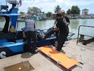 Malaysian officials remove a body from their rescue vessel in Tanjung Sedili, on August 4, 2013