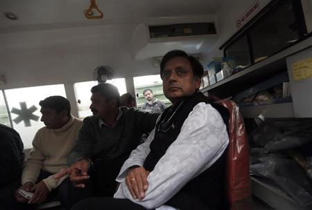 Minister of State for Human Resource Development Shashi Tharoor (R) sits in an ambulance as he waits outside a mortuary to receive his wife Sunanda Puskhar Tharoor's body at a hospital in New Delhi January 18, 2014.REUTERS/Adnan Abidi