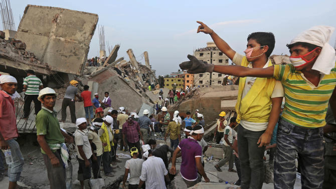 Bangladeshi rescuers from a youth group gesture for help at the site of a building that collapsed Wednesday in Savar, near Dhaka, Bangladesh, Thursday, April 25, 2013. By Thursday, the death toll reached at least 194 people as rescuers continued to search for injured and missing, after a huge section of an eight-story building that housed several garment factories splintered into a pile of concrete. (AP Photo/Kevin Frayer)