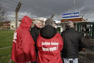 "Labour union members stand at the entrance of the Goodyear tyres factory in Amiens, northern France, in this January 31, 2013 file picture. French trade unionists held two executives overnight on Tuesday January 7, 2014 at the country's Goodyear tyre plant - a flashpoint for France's troubled industrial relations - to demand higher pay-outs for more than a thousand planned layoffs. Workers at the idled factory in the northern city of Amiens have been trying to negotiate redundancy terms with management for nearly a year, after Texan tyre tycoon Maurice Taylor withdrew a potential rescue bid on the grounds that French workers were lazy - triggering a political storm. The message reads ""Goodyear - Gangster Bosses"". Picture taken January 31, 2013. REUTERS/Pascal Rossignol/Files (FRANCE - Tags: BUSINESS EMPLOYMENT)"