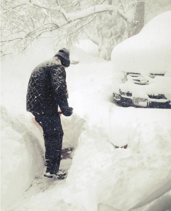 Steven Gros shovels snow from outside his home in Orchard Park