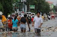 Residents wade through a flooded street filled with rubbish in the town of Navotas, in suburban Manila on August 1, 2012. Rescuers deployed rubber boats while doctors fanned across cramped evacuation centres in the Philippines as the death toll from five days of flooding reached 23 on Thursday, officials said