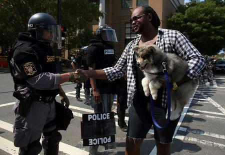 Yankeek Brinson and his friend's husky puppy named Bear greet police in riot gear protecting the city's football stadium from demonstrators protesting the police killing of Keith Scott in Charlotte