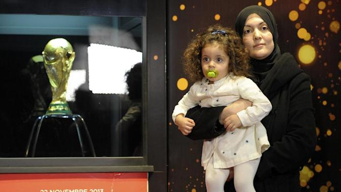 A woman holding her daughter poses for a sponsor photographer next to the FIFA World Cup Trophy, Friday, Nov. 22, 2013 in Algiers.  The trophy arrived Thursday for a two-day exhibition which will open to the public on Friday. The soccer mad country Algeria qualified Tuesday for the 2014 World Cup Finals