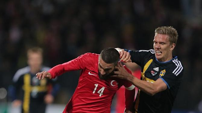 Turkey's Arda Turan, left, vies with Sweden's Pontus Wernbloom during their International Friendly soccer match at 19 Mayis Stadium in Ankara, Turkey, Wednesday, March 5, 2014.(AP Photo)