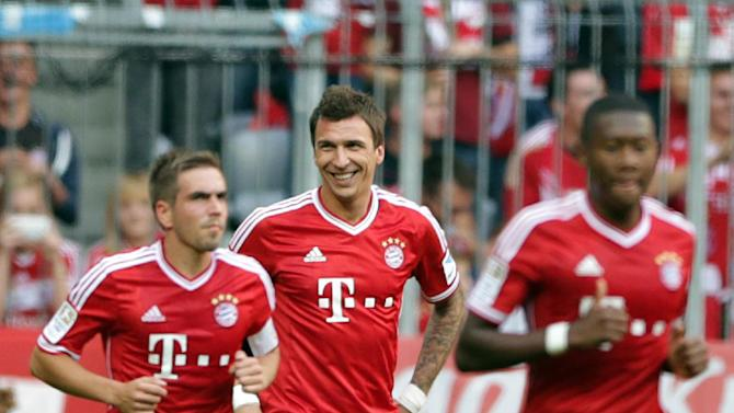 Bayern's Mario Mandzukic of Croatia, center, smiles after scoring his side's first goal  during the German first division Bundesliga soccer match between FC Bayern Munich and Hertha BSC Berlin, in Munich, southern Germany, Saturday, Oct. 26, 2013