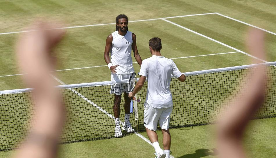 Viktor Troicki of Serbia shakes hands with Dustin Brown of Germany after winning their match as a fan claps at the Wimbledon Tennis Championships in London