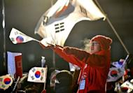 A supporter of South Korea's presidential candidate Park Geun-Hye of the ruling New Frontier Party waves national flags during an election rally in Seoul on December 18, 2012.