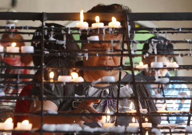 A Catholic devotee lights a candle before attending mass in the Mother of Perpetual Help church in Paranaque city
