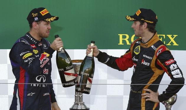 Red Bull Formula One driver Vettel of Germany toasts third-placed Lotus Formula One driver Grosjean of France on podium after winning the Japanese F1 Grand Prix at the Suzuka circuit