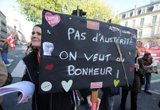 "A woman holds a placard reading ""No austerity, we want happiness"" during a demonstration against austerity in Toulouse, France, on November 14. The rating agency Moody's said on Tuesday that it was studying the impact of its cut of France's top credit notation on the triple ""A"" ratings of eurozone rescue funds that are underpinned in part by France."