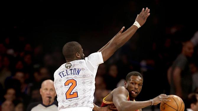 Cleveland Cavaliers' Luol Deng, right, tries to pass around New York Knicks' Raymond Felton, left, and Tim Hardaway Jr. during the first half of an NBA basketball game at Madison Square Garden, Sunday, March 23, 2014, in New York