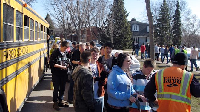 High school students arrive by bus Friday, April 26, 2013, to help place 100,000 sandbags around Fargo, N.D., and help protect homes against Red River flooding. The nearly-annual sandbag party began in 2009 when the city fought the first of three straight major floods. (AP Photo/Dave Kolpack)