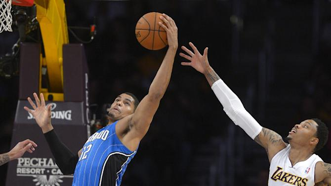 Orlando Magic forward Tobias Harris, left, grabs a rebound away from Los Angeles Lakers guard Kent Bazemore during the first half of an NBA basketball game, Sunday, March 23, 2014, in Los Angeles