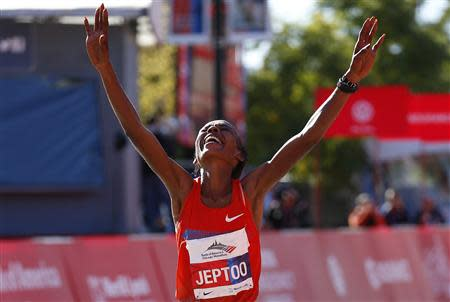 Rita Jeptoo of Kenya celebrates as she crosses the finish line to win the women's division at Chicago Marathon in Chicago, Illinois