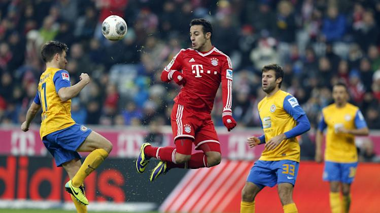 Bayern's Thiago Alcantara of Spain, center, Braunschweig's Kevin Kratz, left, and Braunschweig's Marco Caligiuri challenge for the ball during the German first division Bundesliga soccer match between FC Bayern Munich and Eintracht Braunschweig, in Munich, southern Germany, Saturday, Nov. 30, 2013