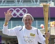 England legend goalkeeper Gordon Banks carries the Olympic Torch in front of Wembley Stadium in west London, two days before the start of the London 2012 Olympic Games