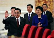 China's new Premier, Li Keqiang (2nd R), waves to journalists as he arrives together with his vice premiers, (from L) Zhang Gaoli, Wang Yang, Liu Yandong and Ma Kai, for his first press conference after the closing session of the National People's Congress, at the Great Hall of the People in Beijing, on March 17, 2013