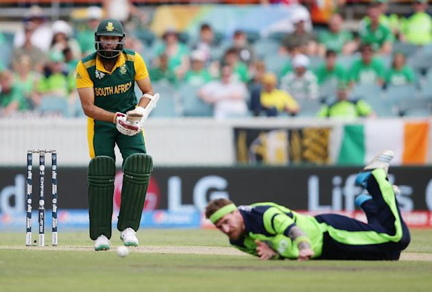 South Africa's Hashim Amla, left, watches as Ireland's John Mooney falls while fielding the ball during their Cricket World Cup Pool B match in Canberra, Australia, Tuesday, March 3, 2015. (AP