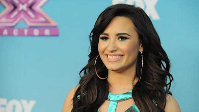 "In this Dec. 20, 2012 photo, Demi Lovato attends the ""The X Factor"" season finale results show at CBS Television City in Los Angeles. Fox network says Lovato is returning as a judge of ""The X Factor."" The singer-songwriter will be back alongside series creator Simon Cowell when the singing competition begins its third season this fall. (Photo by Jordan Strauss/Invision/AP)"