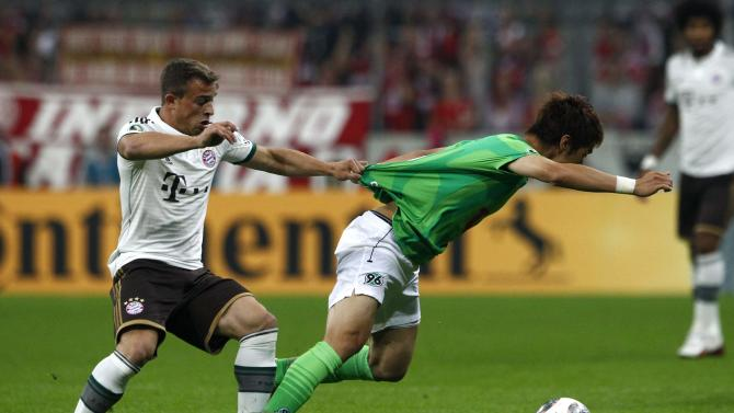 Bayern Munich's Shaqiri challenges Sakai of Hanover 96 during German soccer cup match in Munich