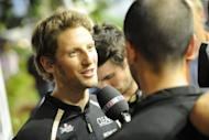 Lotus driver Romain Grosjean of France speaks to television reporters at the paddock ahead of Singapore's Formula One night race. Grosjean said he hoped to come back a stronger driver at the Singapore Grand Prix after his one-race ban for causing a dangerous pile-up in Belgium