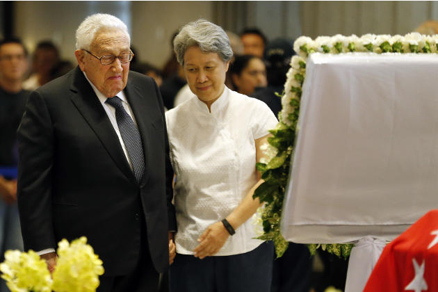 Former U.S. Secretary of State Henry Kissinger, left, is accompanied by Ho Ching, right, wife of Singapore's Prime Minister Lee Hsien Loong, as he pays his respects to the late Lee Kuan Yew, Satur