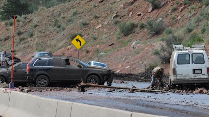 A man works to dig out his van from the mud on Hwy. 24 just west of Manitou Springs, Colo. when a wall of mud came down on vehicles during a rainstorm on Wednesday, July 10, 2013. The flash flood occurred in the area of where the Waldo Canyon Fire was last year. (AP Photo/The Gazette, Jerilee Bennett)