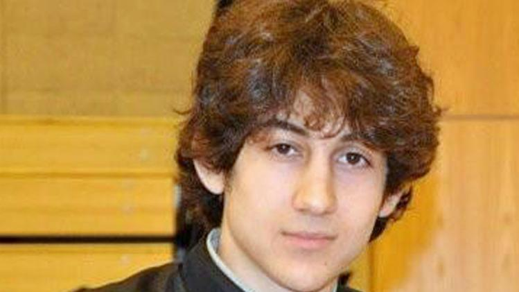 In this undated photo provided by Robin Young, Dzhokhar A. Tsarnaev, poses for a photo after graduating from Cambridge Rindge and Latin High School. Tsarnaev has been identified as the surviving suspect in the marathon bombings. Two suspects in the Boston Marathon bombing killed an MIT police officer, injured a transit officer in a firefight and threw explosive devices at police during a getaway attempt in a long night of violence that left one of them dead and another still at large Friday, April 19, 2013. (AP Photo/Robin Young)