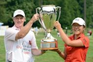 Amateur Lydia Ko of New Zealand and caddie Brian Alexander pose with the trophy after the final round of the Canadian Women's Open at The Vancouver Golf Club in Coquitlam, Canada. Ko became the youngest champion in the history of the LPGA Tour by firing a five-under-par 67