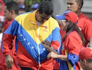 "Venezuelan President Nicolas Maduro dances with First Lady Cicilia Flores during a traditional May Day rally in Caracas on May 1, 2013. Maduro said Washington was making a ""grave mistake"" in not acknowledging his victory in the controversial April 14 presidential election"