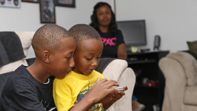 CORRECTS SPELLING OF CHILD'S NAME TO CAM'RON, NOT CAMERON- Cam'ron Richardson, left, plays a video game with his little brother, Anthony Richardson, right, as his mother watches, rear, at their home in Moore, Okla., Friday, Aug. 16, 2013, before leaving home for the first day of school for Plaza Towers Elementary school in their temporary location at Central Jr. High school in Moore, Okla., Friday, Aug. 16, 2013. The Briarwood and Plaza Towers elementary schools were destroyed when an EF5 twister hit Moore on May 20. Cam'ron was trapped under the rubble of the tornado that killed two dozen people. (AP Photo/Sue Ogrocki)