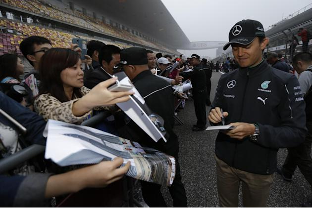 Mercedes driver Nico Rosberg of Germany, right, signs autographs for fans during an autograph session ahead of Sunday's Chinese Formula One Grand Prix at Shanghai International Circuit in Shanghai