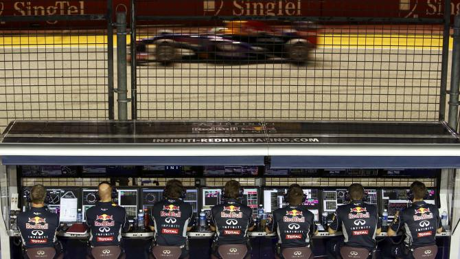 Red Bull Formula One driver Vettel passes Red Bull engineers during the qualifying session of the Singapore F1 Grand Prix in Singapore