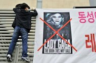 "A member of South Korea's Alliance for Sound Culture In Sexuality puts up a street banner against Lady Gaga's Seoul concert in downtown Seoul on April 23. Accused of contaminating youngsters with ""satanic"" dance moves and ""intolerable"" outfits, the cult of Lady Gaga is on a collision course with Asia's moral guardians ahead of her mammoth world tour"