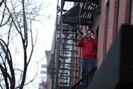 A neighbour takes a picture with his mobile phone outside the apartment where actor Philip Seymour Hoffman was found dead in Manhattan, New York February 2, 2014. REUTERS/John Taggart