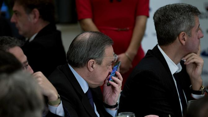 "Real Madrid's President Florentino Perez, centre, speaks on a cell phone next to Atletico de Madrid's CEO, Miguel Angel Gil Marin, right during a breakfast sports meeting in a hotel in Madrid, Spain, Thursday, Dec. 19, 2013. Spanish sports leaders are angry over a European Union probe targeting Real Madrid, Barcelona and five other top Spanish soccer clubs for possibly having received illegal state aid, and claim someone is out to attack Spanish football. Miguel Cardenal, head of the Superior Sports Council, Spain's top sporting body, said Thursday the probe was causing ""grave damage "" to Spanish soccer's reputation and questioned the motives behind the EU investigation. Real Madrid president Florentino Perez was equally annoyed and said he believed ""there is a campaign against Spanish football."""