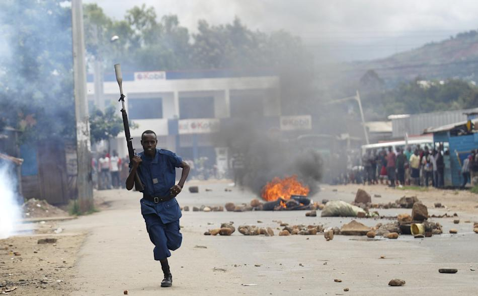 Riot policeman runs past a bonfire during street protests in Burundi's capital Bujumbura