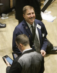 FILE - In this April 25, 2007 file photo, a trader smiles as he works on the floor of the New York Stock Exchange. The stock market's best-known indicator surged past its latest milestone shortly after trading began Wednesday, and even made it past 13,100, to close at 13,098.89. When it comes to Wall Street, big, round numbers make people take notice. Dow 13,000, reached earlier this week for a few brief minutes, was the latest example. (AP Photo/Richard Drew, File)