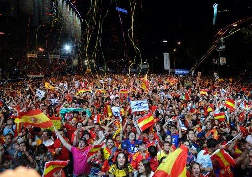 Supporters of Spain's national football team wave national flags in Madrid