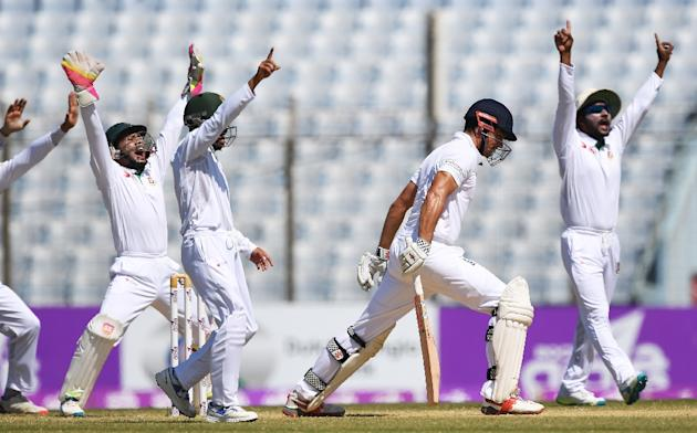 Bangladesh captain Mushfiqur Rahim (L) and teammates appeal unsuccessfuly for the wicket of England's captain Alastair Cook (2R) during the third day of the first Test in Chittagong on October 22,