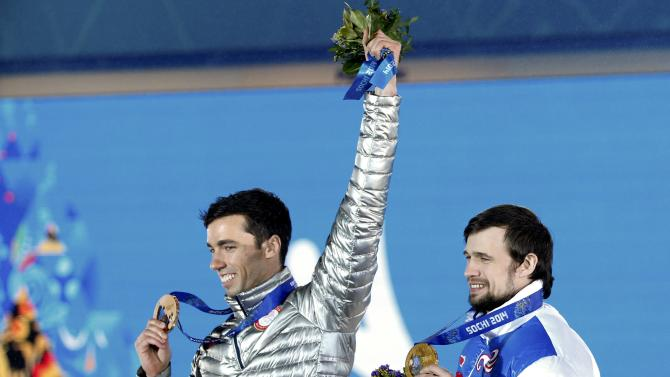 Gold medallist Tretiakov of Russia and bronze medallist Antoine of the U.S. celebrate during the victory ceremony for the men's skeleton event at the 2014 Sochi Winter Olympics in Sochi