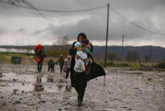 A migrant carries her child after crossing the border from Greece into Macedonia, near Gevgelija