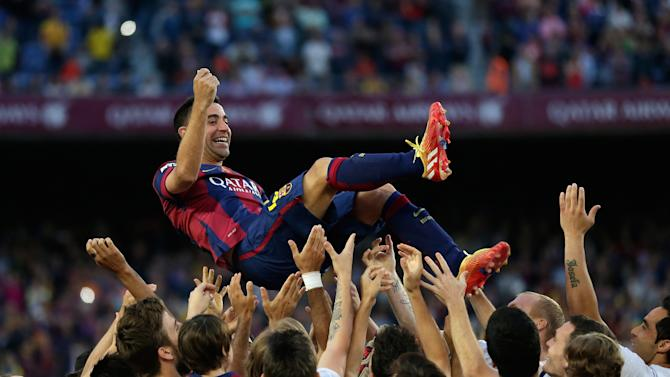 FILE - In this May 23, 2015 file photo FC Barcelona's Xavi Hernandez is thrown into the air by his teammates after winning the Spanish League title, at the end of their Spanish La Liga last round soccer match against Deportivo Coruna at the Camp Nou stadium in Barcelona. Hernandez said he will leave the Catalan club after 17 trophy-laden seasons in which he set club records for appearances and titles won. (AP Photo/Manu Fernandez, file)