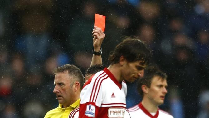 Referee Moss shows a red card to Fulham's Amorebieta during their English Premier League soccer match against Manchester City at the Etihad stadium in Manchester
