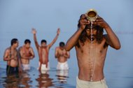 Hindu devotees pray as they bathe in the Sangam or confluence of the Yamuna, Ganges and mythical Saraswati rivers at the Kumbh Mela in Allahabad, on February 10, 2013
