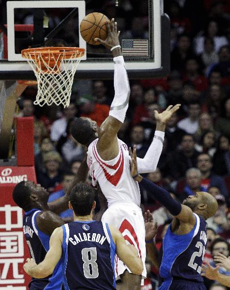 Houston Rockets forward Dwight Howard (12) shoots over Dallas Mavericks guard Vince Carter, right, and center Samuel Dalembert, left, as guard Jose Calderon (8) looks on during the first half of an NBA basketball game, Monday, Dec. 23, 2013, in Houston