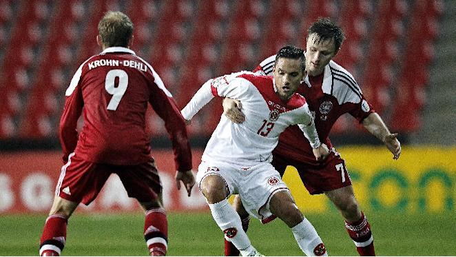 Malta's Andre Schembri, center, is challenged by Denmark's Michael Krohn-Dehli, left, and William Kvist during their group B World Cup qualifying soccer match in Parken, Copenhagen, Tuesday Oct. 15, 2013