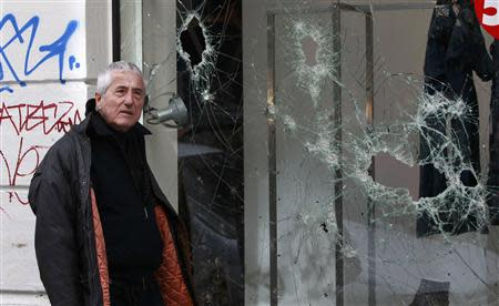 A man passes smashed store windows after a night of violence following the Greek parliament approval of a deeply unpopular austerity bill in Athens